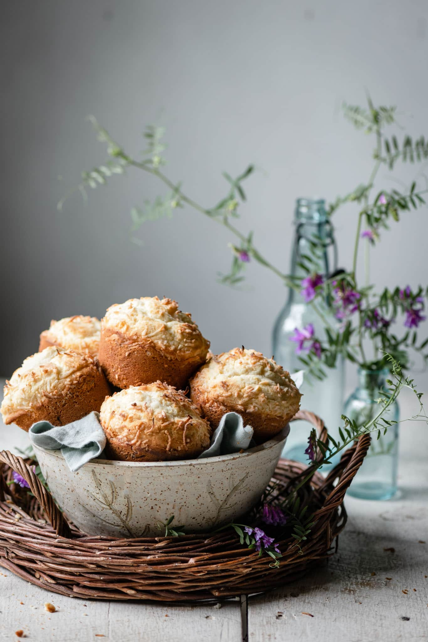 Bowl full of coconut topped muffins on a white table next to flowers.