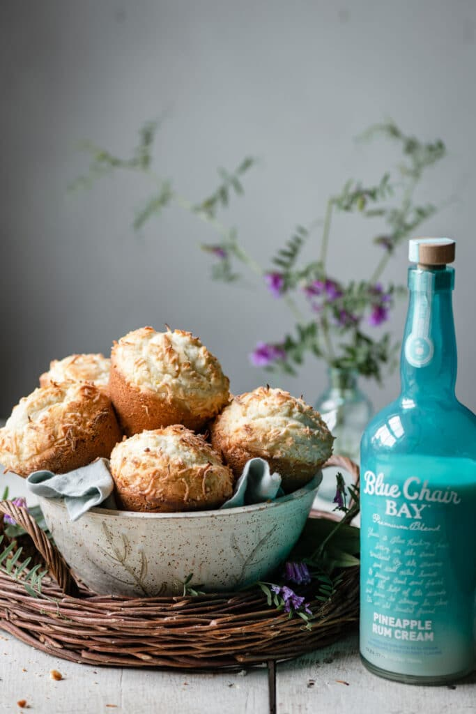 Bowl of coconut muffins on table next to bottle of pineapple rum.