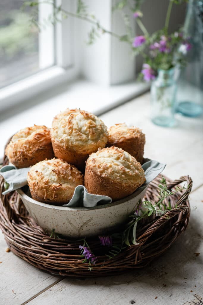 Bowl of coconut pineapple muffins on table next to window.