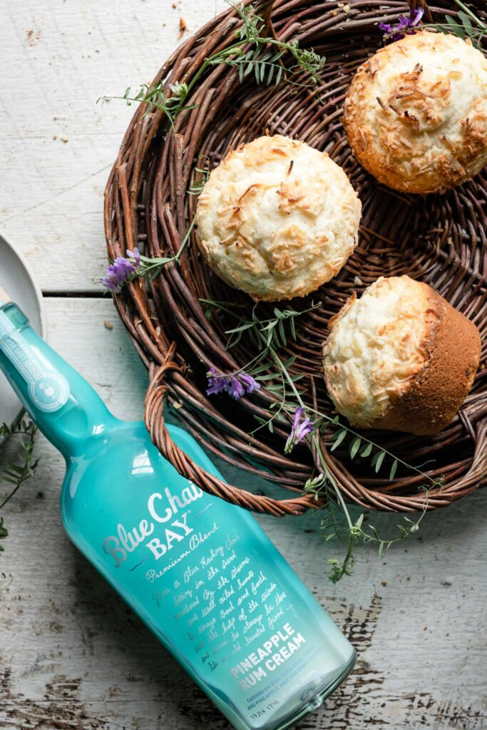 Muffins in a basket next to a bottle of Blue Chair Bay Pineapple Rum Cream on table.