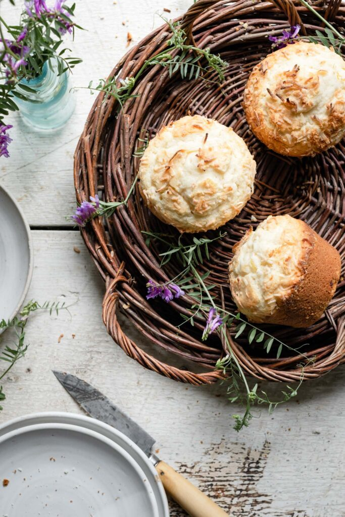 Above view of muffins topped with coconut in a brown basket.