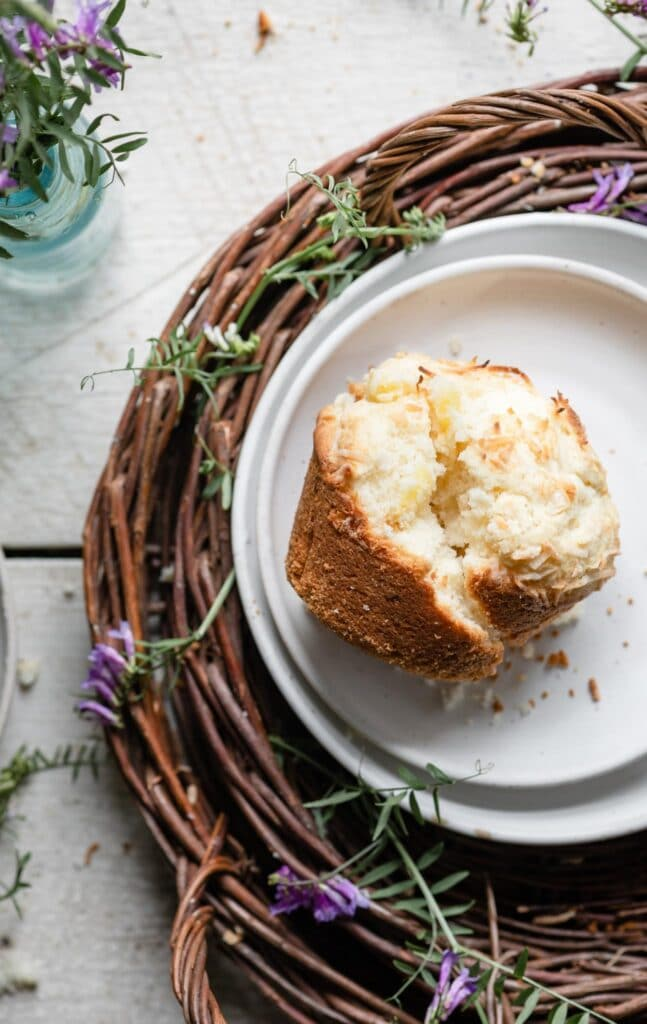 Single pineapple muffin on a plate cut in half next to purple flowers.