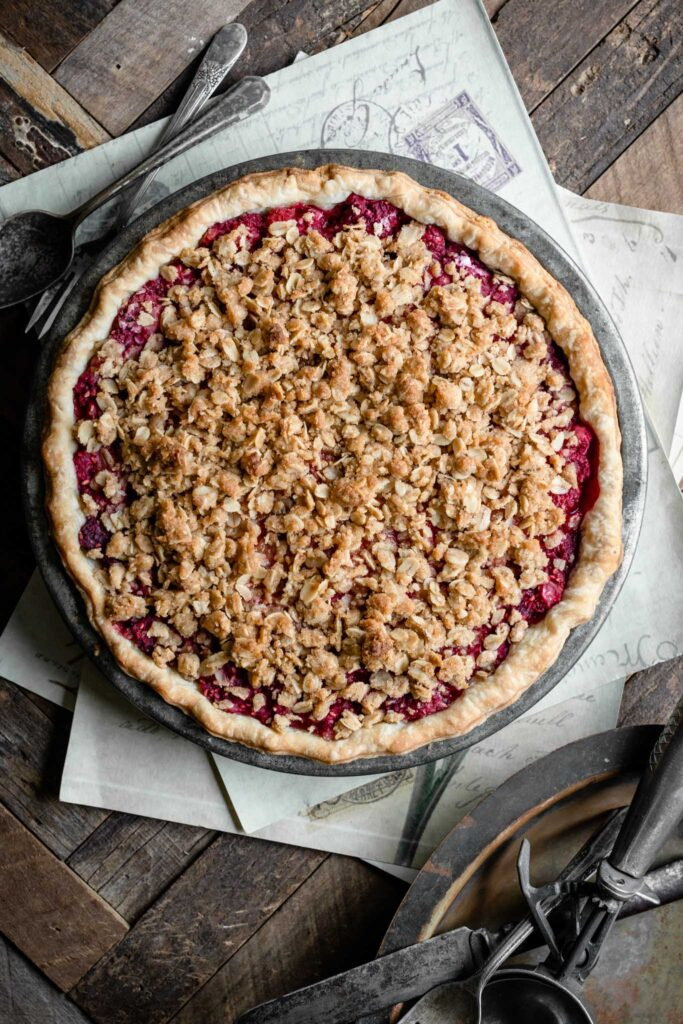 A whole pie on table filled with raspberries and topped with a crumble crust.