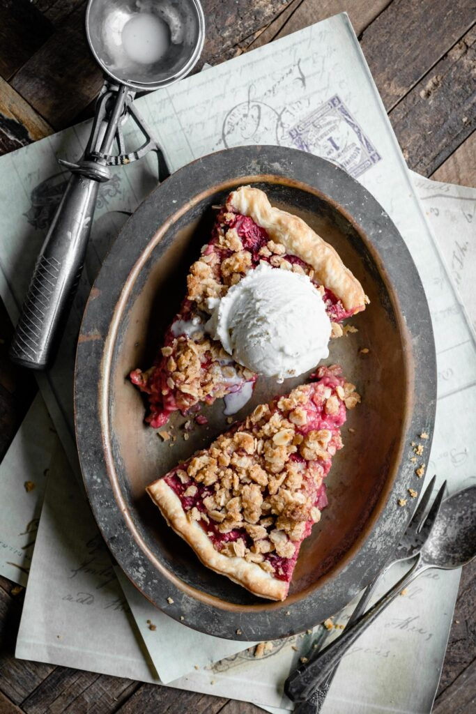 Slices of raspberry pie on a metal plate with a scoop of ice cream.