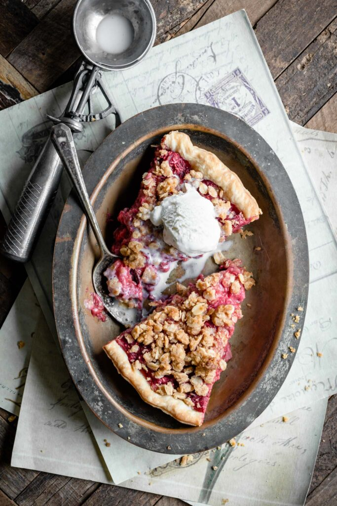 Two slices of raspberry pie in a metal dish topped with melted vanilla ice cream.