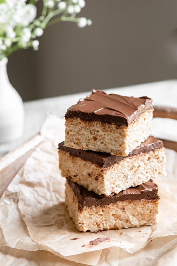 Three square sliced chocolate covered rice krispie treats in a stack on white table.