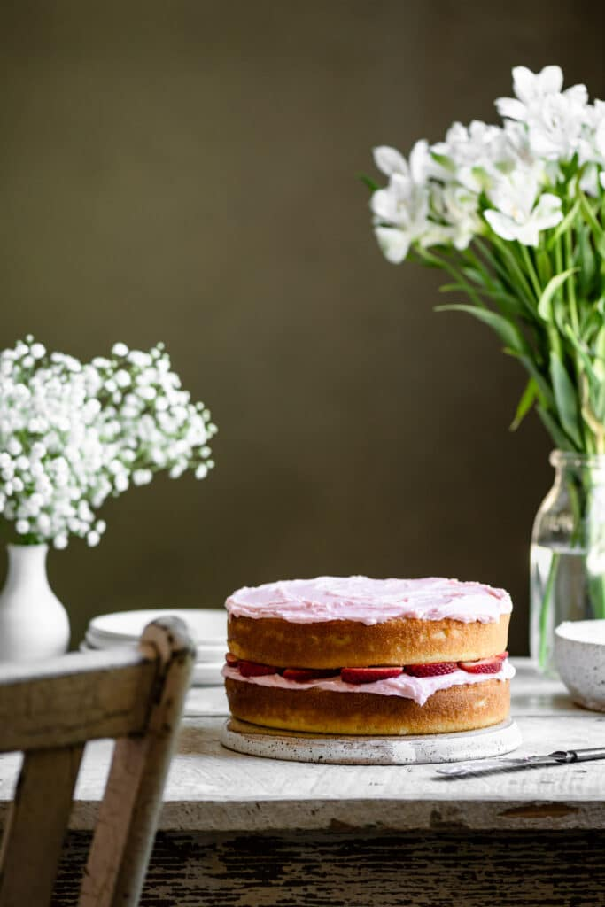 Layer cake with pink frosting on a white table next to vase of flowers.