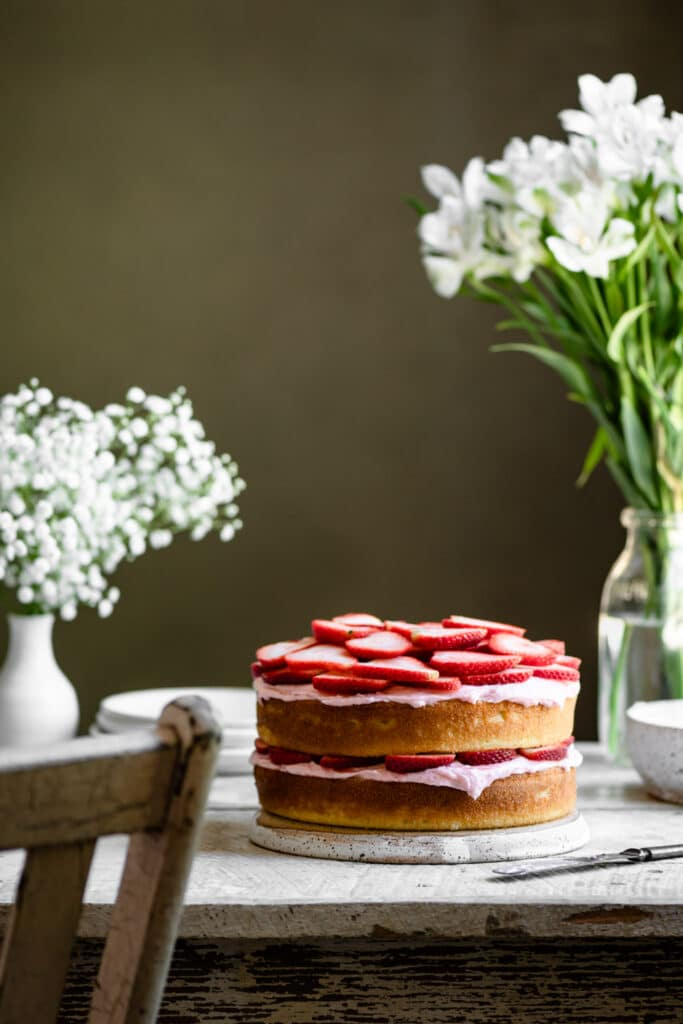 Two layer lemon cake topped with sliced strawberries on table next to flowers.