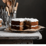 Recipe card for carrot cake with a photo of a whole cake missing a slice.