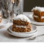 Recipe card with a picture of carrot cake slice on white plate topped with shredded coconut.
