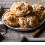 Recipe card for rosemary cheddar biscuits with photo of biscuits in plate on table.