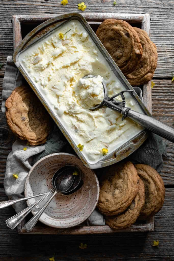 Banana Ice Cream in a loaf tin surrounded by large chocolate chip cookies.