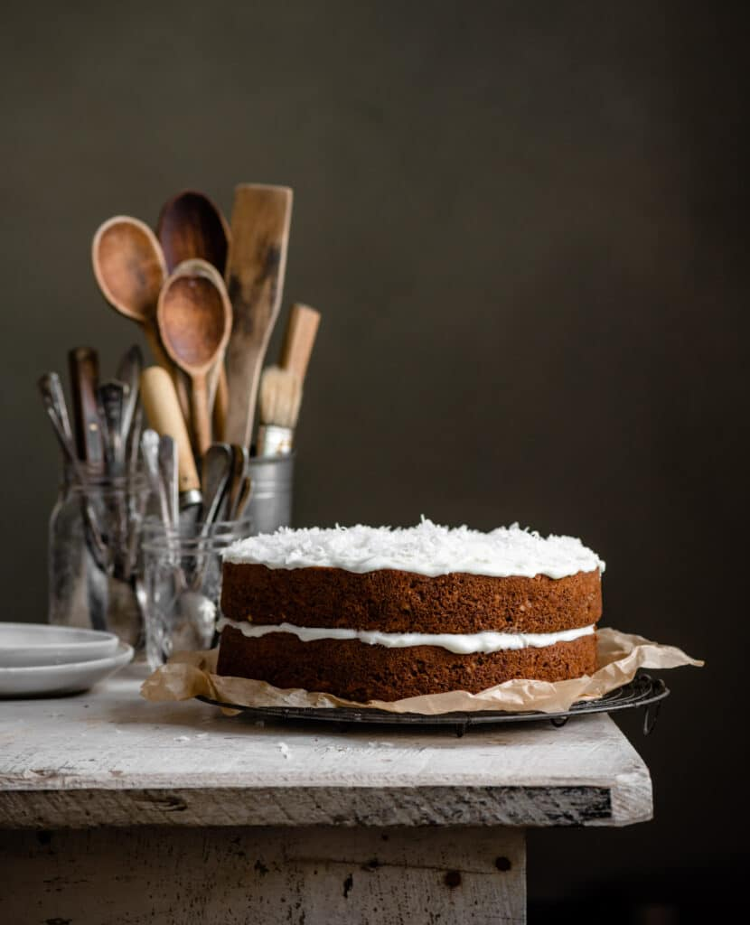 Two layered carrot cake with coconut icing on a white table next to jars of spoons.