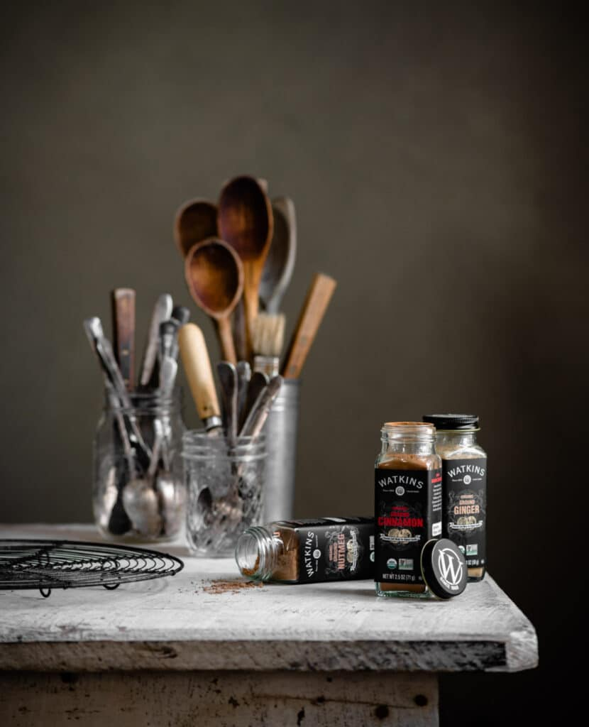 White wood table with jars of baking spices and glass jars filled with spoons.