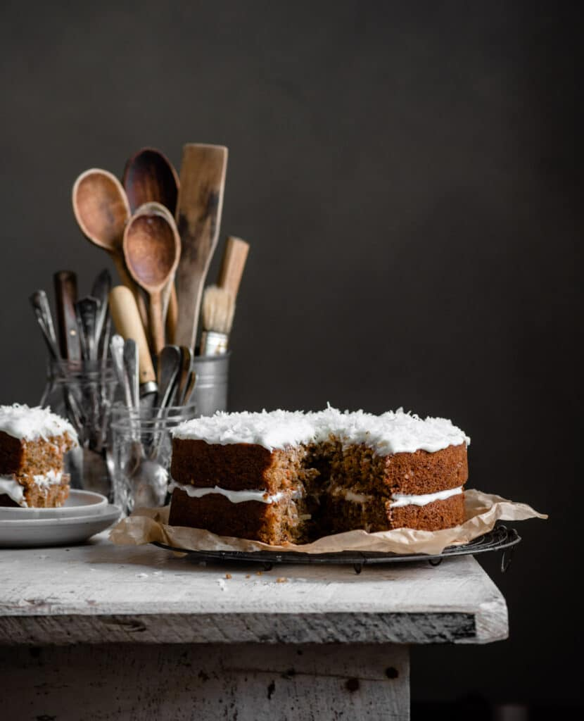 Two layered carrot cake on table with a slice missing.