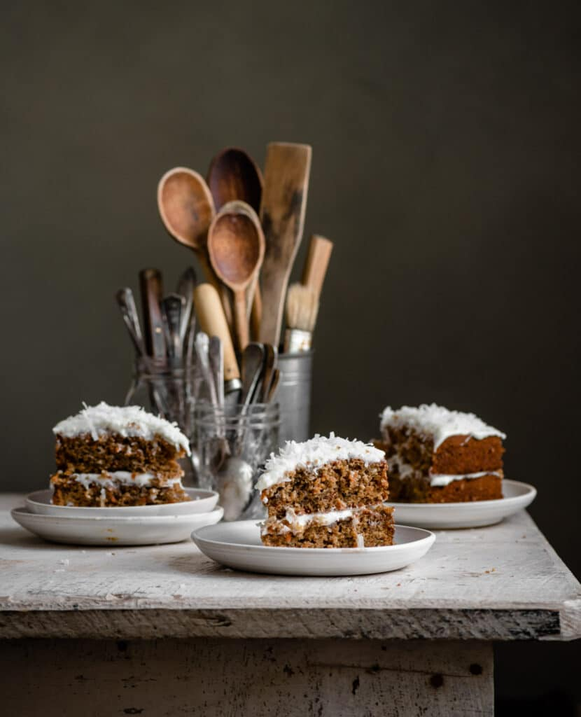 Three slices of cake topped with shredded coconut on a white wood table.