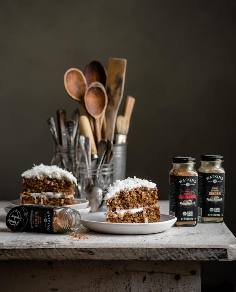 Two slices of carrot cake next to spice jars on a wood table.