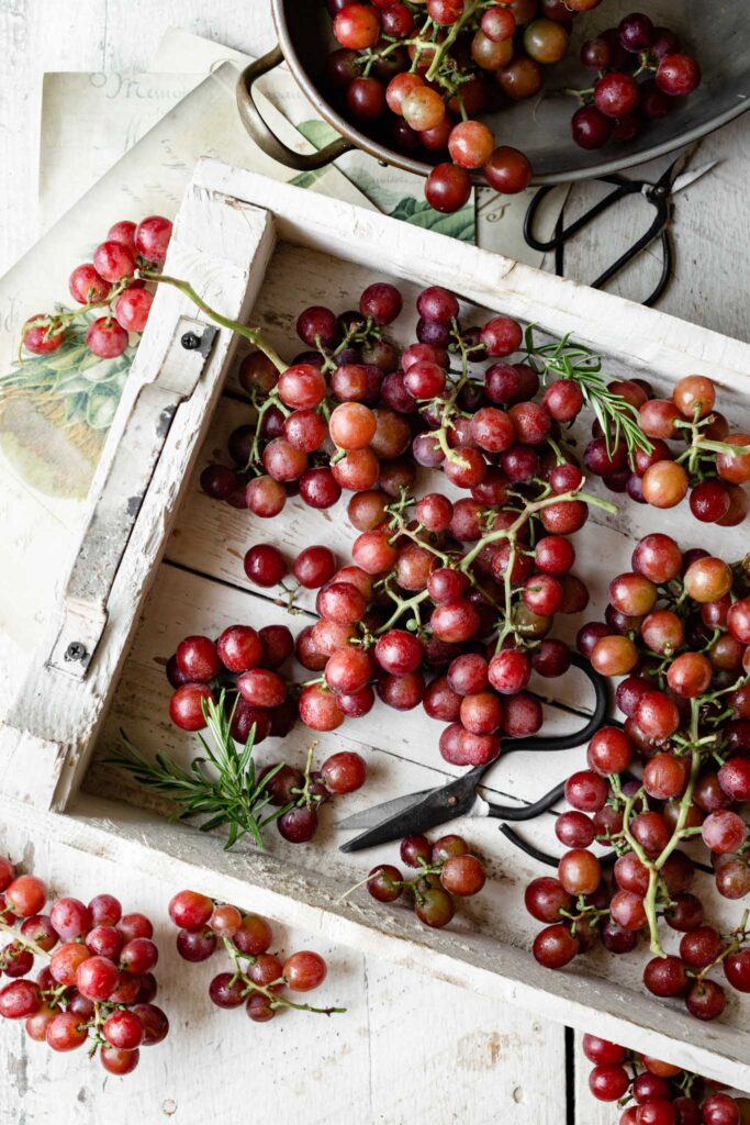 Fresh red grapes in a white wooden box with sprigs of rosemary.