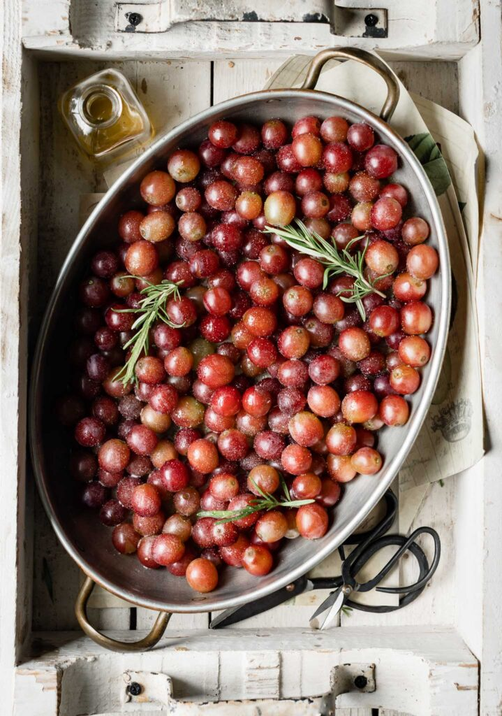 Oval baking pan filled with roasted red grapes.
