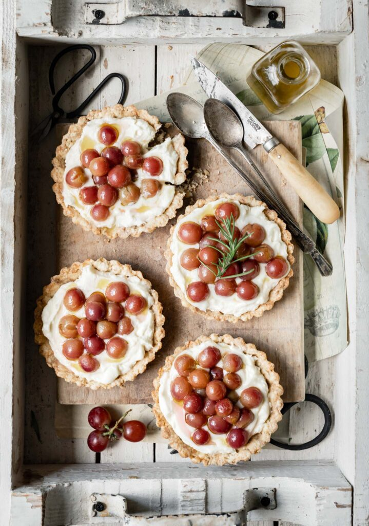 Four mini mascarpone tarts topped with red grapes in a wooden box.