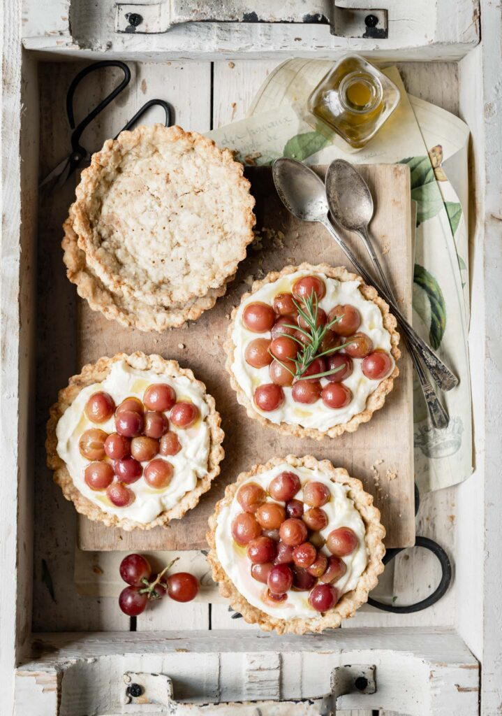 Tart shells filled with mascarpone cheese and topped with red grapes.