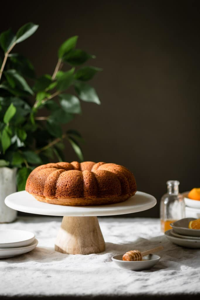 Brown butter bundt cake on cake stand surrounded by white pottery.