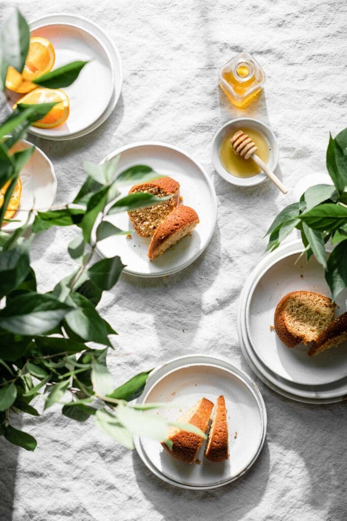 SLices of orange bundt cake on white plates with a bowl of honey and green plants in vases.