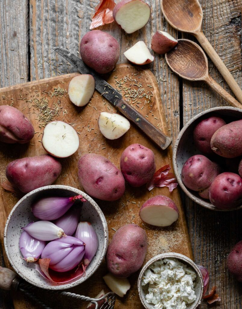 Red skin potatoes on cutting board next to a bowl of peeled shallots.