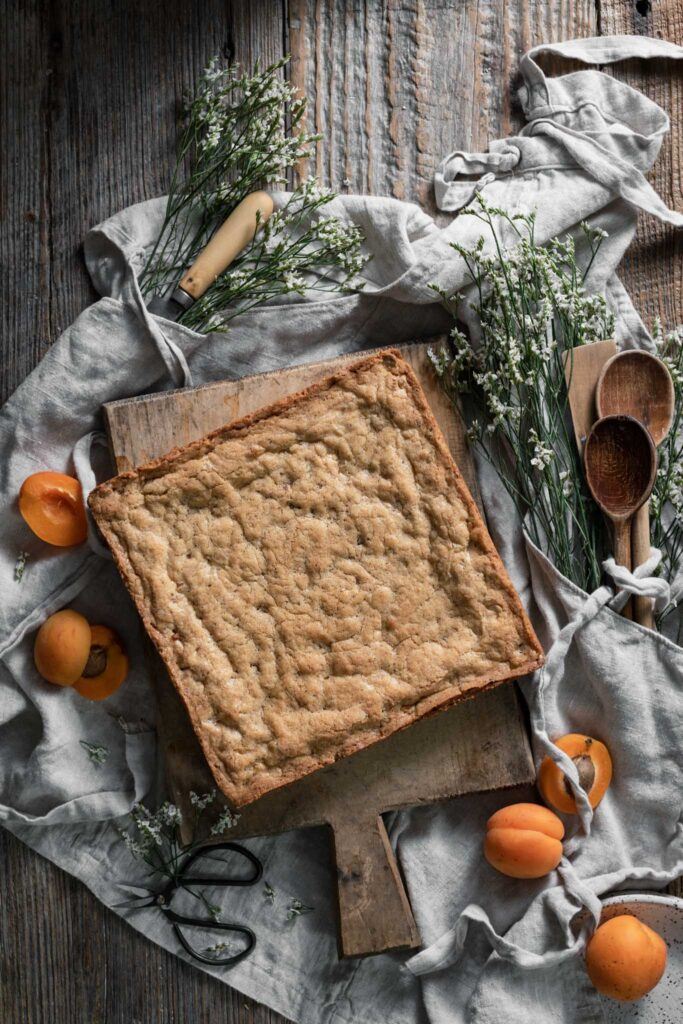 Uncut square of brown butter blondies on cutting board next to flowers and apricots.