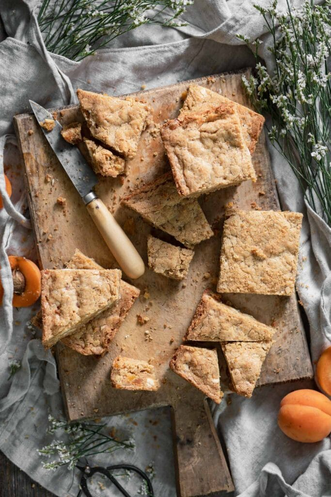 Sliced white chocolate blondies on a wooden cuttingboard.
