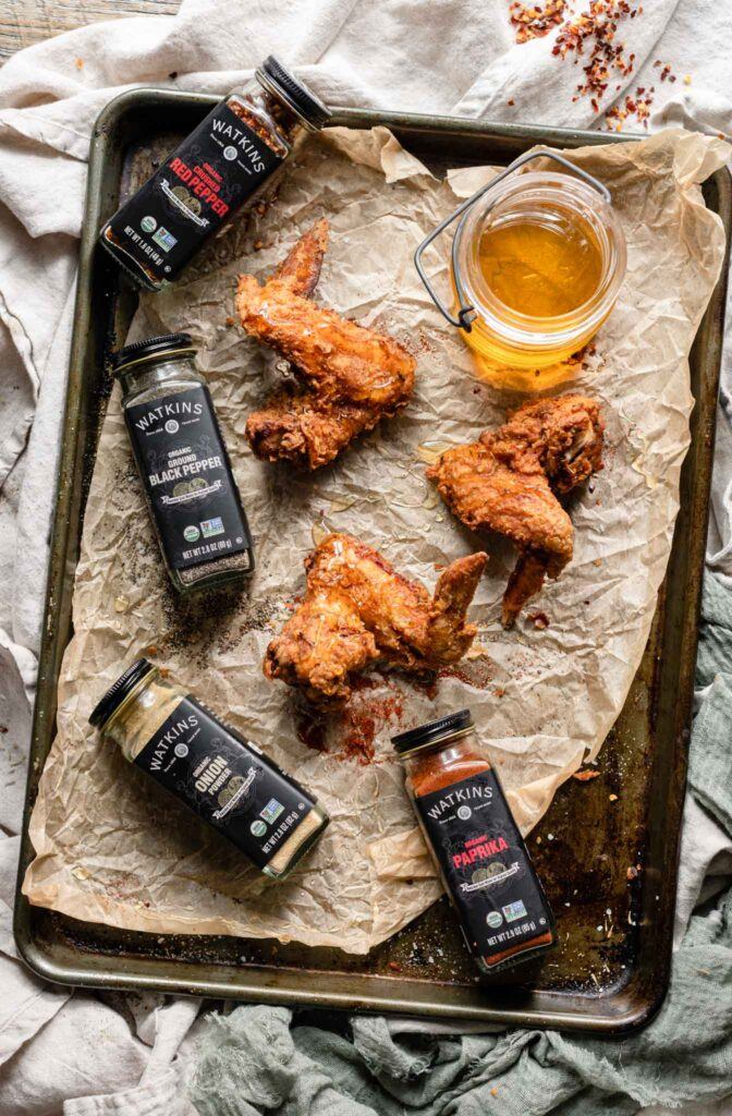 Three chicken wings on a pan next to spice jars and glass jar of honey.