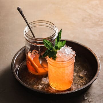 Orange cocktail in mason jar filled with ice and a mint garnish.