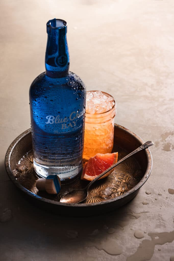Bottle of coconut rum in a tray with cocktail and slice of grapefruit.