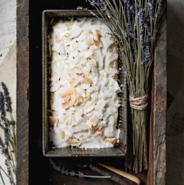 Iced coconut bread in loaf pan inside old wooden box with dried lavender.