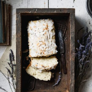Sweet bread covered with vanilla glaze and toasted coconut in a wooden box on table.