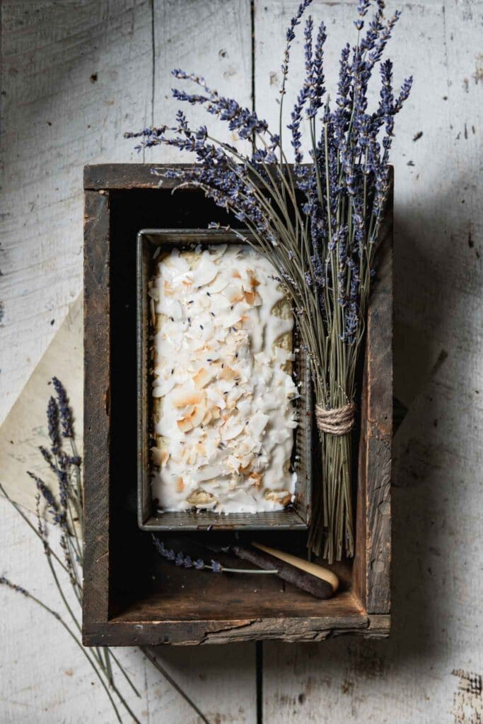 Coconut bread in a wooden box next to bouquet of lavender.