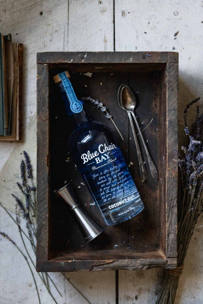 Blue bottle of coconut rum in a wood box on white table.