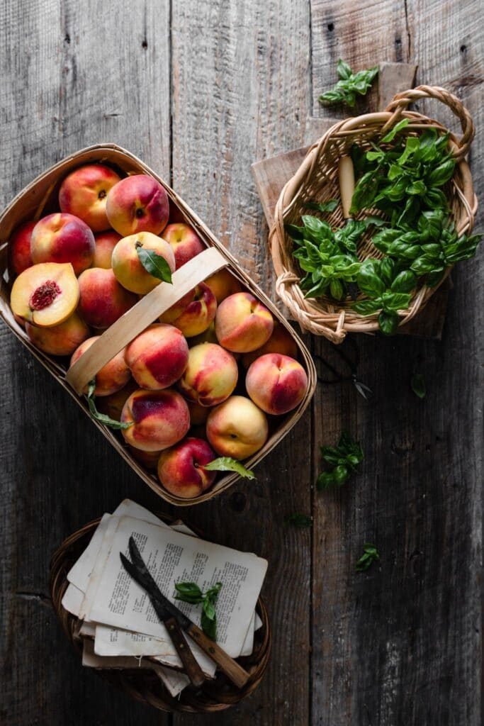 Basket of peaches and basil on a wooden table.
