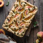 Peach focaccia bread loaf on cutting board.