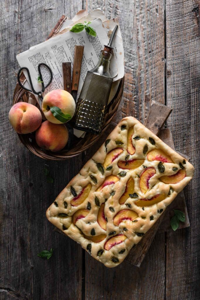 Baked Focaccia bread with peaches and basil next to a basket of peaches and olive oil on wood table.