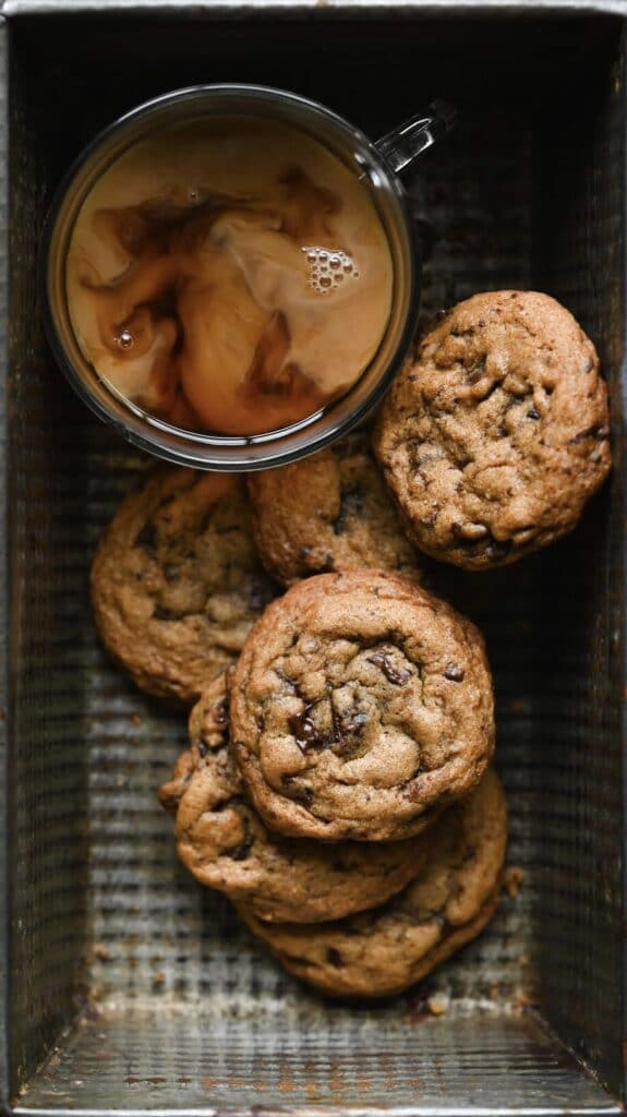 Cup of coffee and stack of chocolate chip cookies in a metal baking pan.
