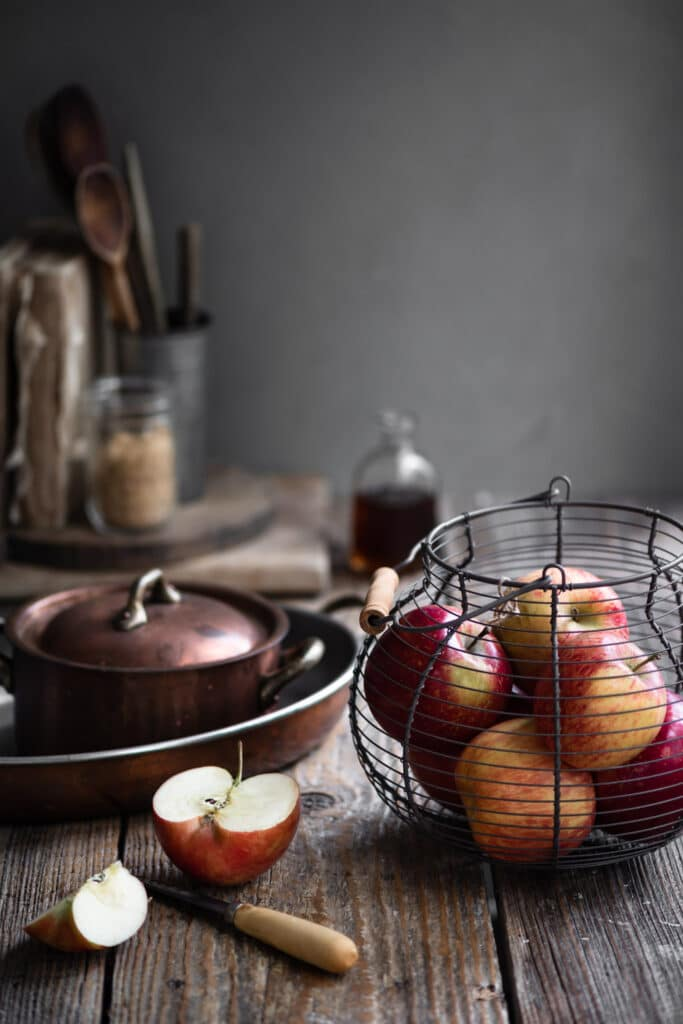 Apples in a wire basket on old wood table next to cooking pots.