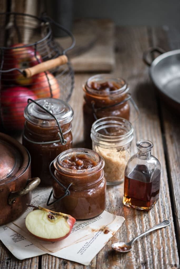 Jars filled with apple butter on wooden table with maple syrup.