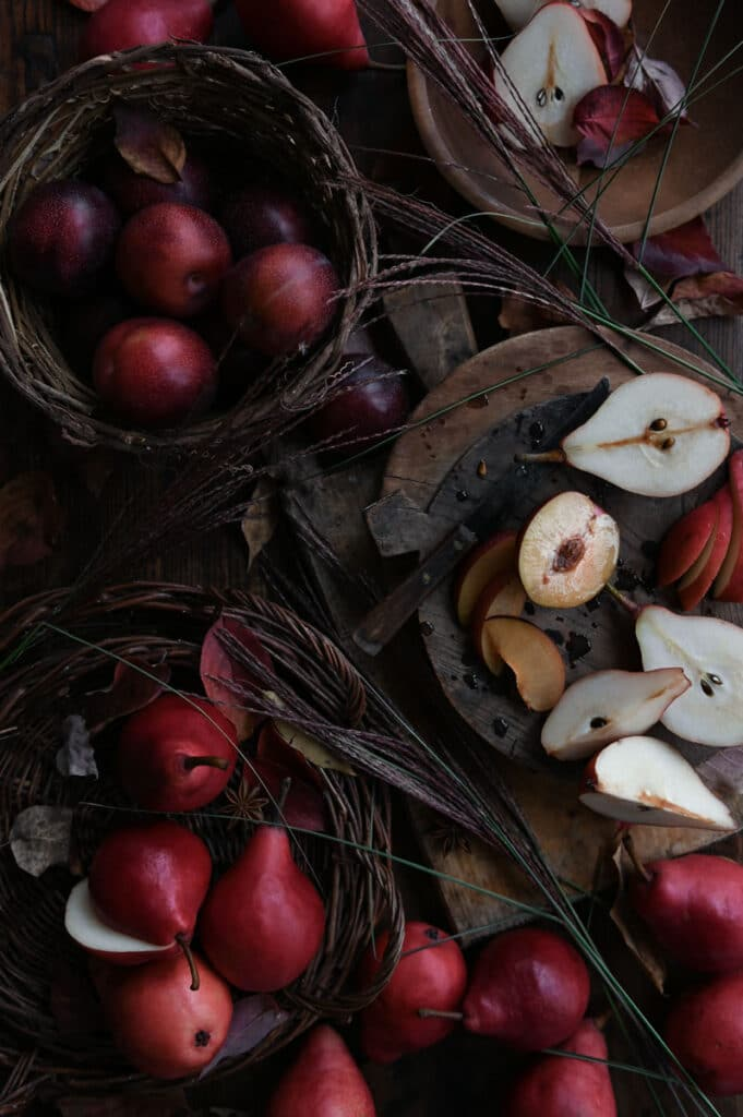 Pears and plums on cutting boards and in a basket on wood table.