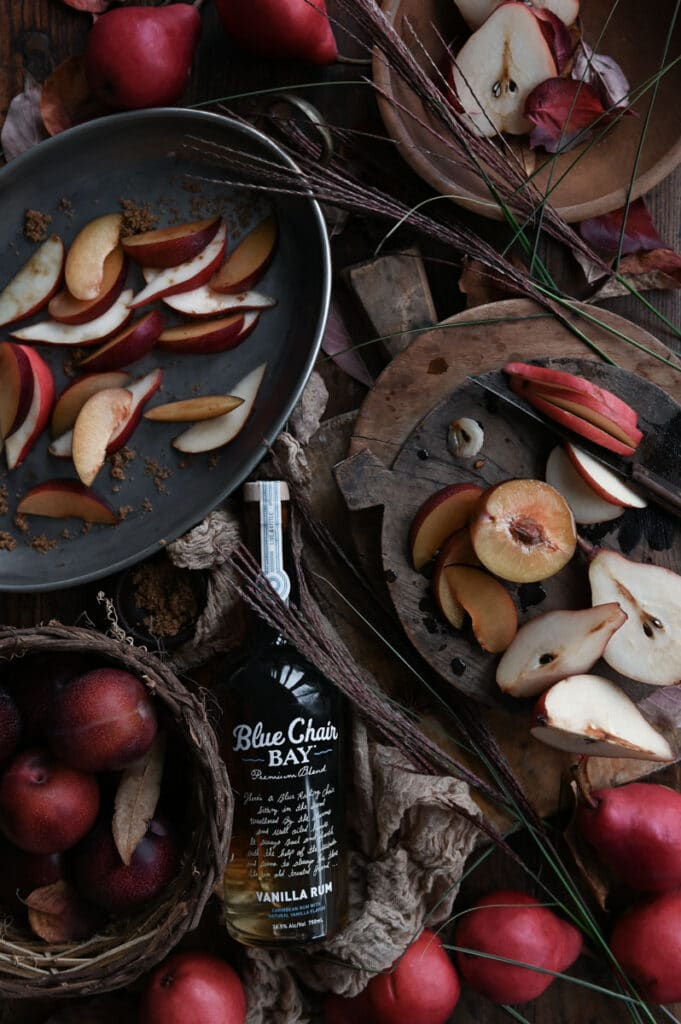 Pears and plums on cutting boards and in a basket next to a bottle of rum on wood table.