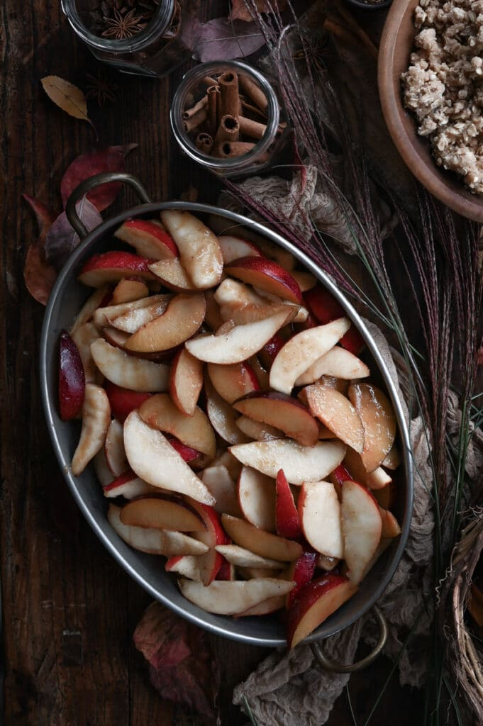 Baking dish filled with sliced pears and plums on wood table.
