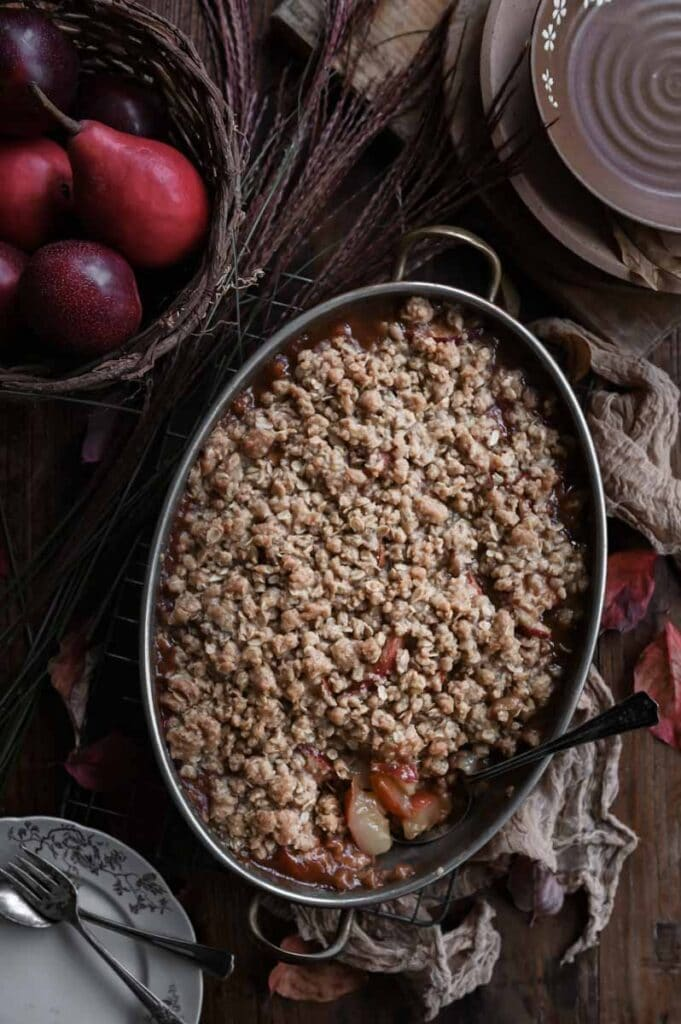 Baked fruit crisp on wood table with a serving spoon scooping out the filling.