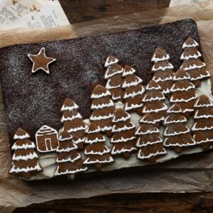 Rectangular gingerbread sheet cake topped with Christmas tree cookies.