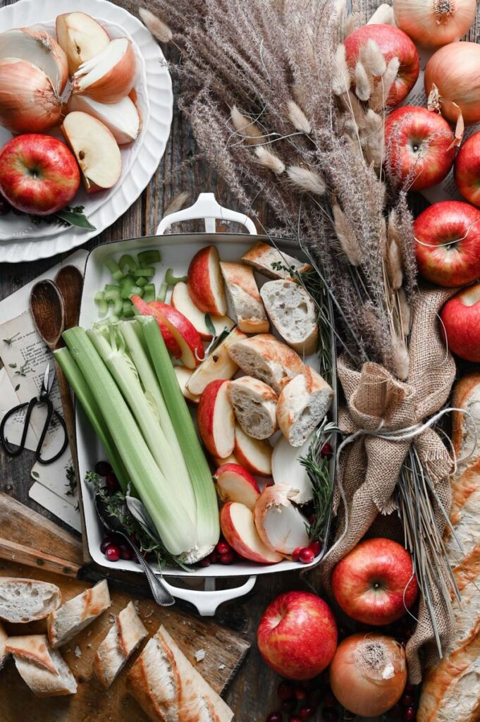 Wood table covered in sliced french bread, celery, apples, and yellow onions around a white casserole dish.