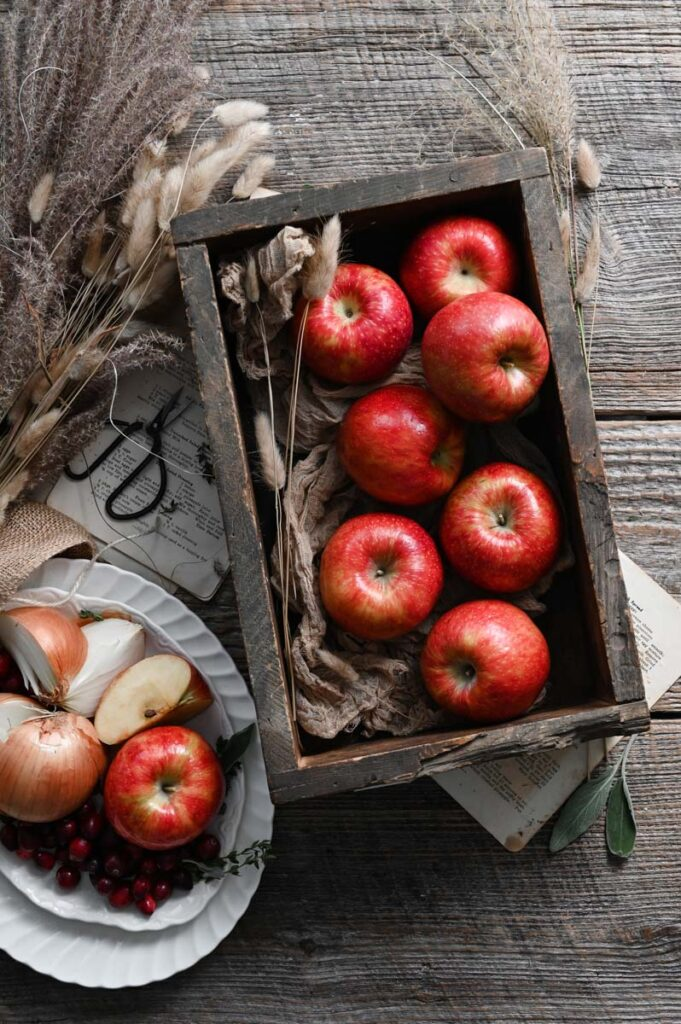 Red apples in a wooden box next to a plate of sliced onions on an old wood table.